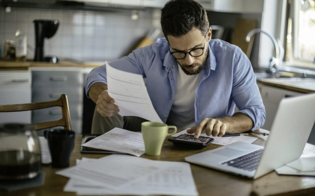 Home Business Insurance, photo of man working from home with laptop, calculator and papers