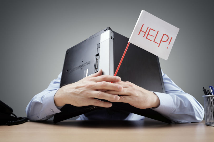 Beating burnout, man hiding behind laptop holding a sign saying help